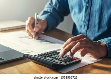 businessman working on desk office with using a calculator to calculate budget, finance concept