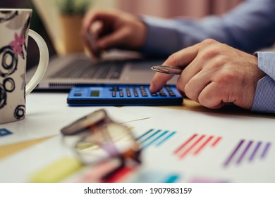 Businessman working on desk office with using a calculator to calculate the numbers