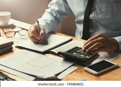 businessman working on desk office with using a calculator to calculate the numbers, finance concept