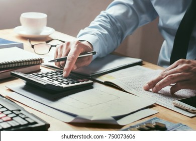 businessman working on desk office with using a calculator to calculate the numbers, finance accounting concept - Shutterstock ID 750073606