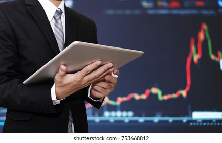 Businessman working on digital tablet with raising financial, stock exchange graph background. Investment in stock exchange