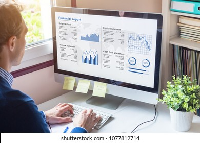 Businessman working on Financial Report of corporate operations on computer screen with Balance Sheet, Income Statement, and key performance indicators