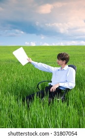 Businessman working on green grassland under blue sky