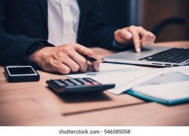 Businessman working on his wooden table in the office with calculator,document,smart phone,pen and laptop in business,finance and banking concept