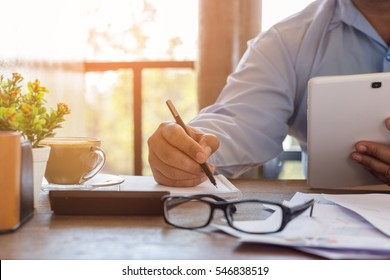 Businessman working on Home office, Watching something on smart Tablet, He was thinking about something for idea and Writing something on notebook, Blurred background, Business concept.