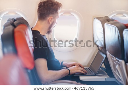 Businessman working on laptop at airplane, Man typing text on laptop at plane, Close up of professional businessman in black t-shirt working on new project, blurred background, shallow DOF.