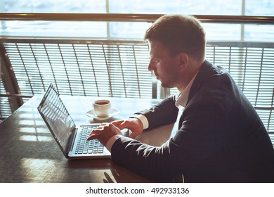 businessman working on laptop in airport cafe, business travel, checking emails and drinking coffee