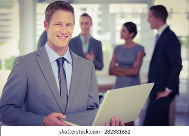 Businessman working on laptop with colleagues behind him in the office