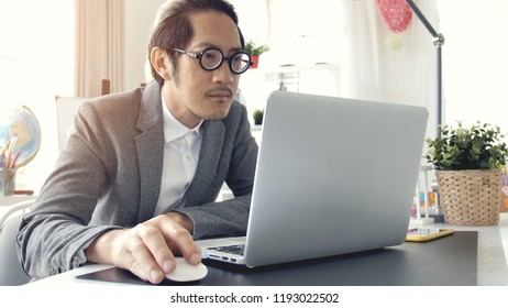 Businessman working on laptop computer in the office, Asian business man wearing eyeglass in office.