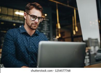 Businessman working on laptop computer sitting in a restaurant. Man managing business work sitting in a restaurant.