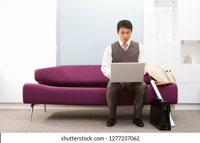 Businessman working on laptop computer on sofa in office reception