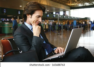 Businessman working on laptop computer at airport