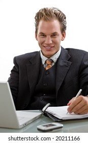 Businessman working on laptop computer, smiling, white background