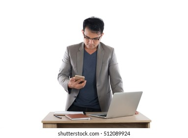 Businessman working on laptop and holding smartphone, white background.