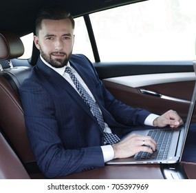 Businessman working on laptop keyboard sitting in car