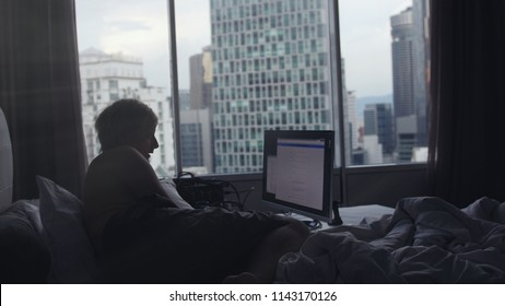 Businessman is working on laptop lies on bed by the window on building on the background