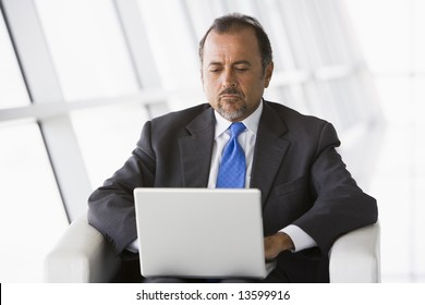 Businessman working on laptop in office lobby