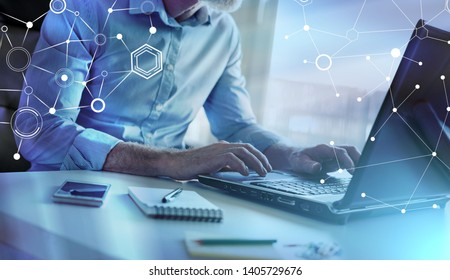 Businessman working on laptop in office; multiple exposure