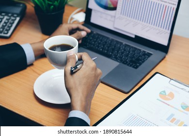 businessman working on laptop in office and a cup of coffee, graph and chart on the desk.