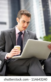 Businessman Working On Laptop Outside Office With Takeaway Coffee