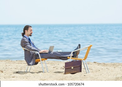 Businessman working on laptop on seaside