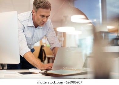 Businessman working on laptop while leaning at desk in office