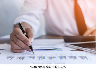 Businessman working on office desk, Watching something on Calculator. He was thinking about something for idea and make a Note something of Idea, Blurred background, Business concept.