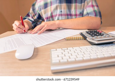 Businessman working on office desk with Calculator, a computer, a pen and papers. Businesses concept.