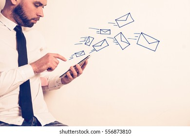 Businessman working on a pad, drawn letter icon flying out from a tablet