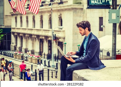 Businessman working on street in New York. Dressing in blue suit, a young guy with beard, sitting outside office building, looking down, reading, typing on laptop computer. Instagram filtered effect.
