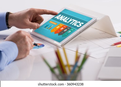 Businessman working on tablet with ANALYTICS on a screen
