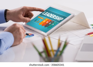 Businessman working on tablet with LEADERSHIP on a screen