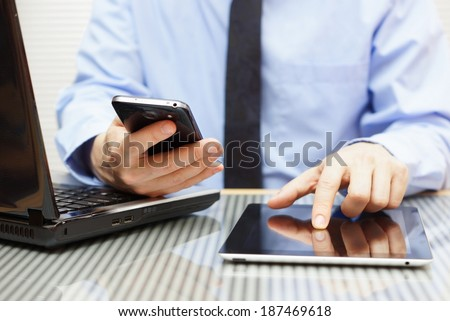 businessman is working on tablet and using smart phone in office with laptop