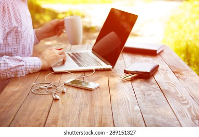 Businessman working outdoor. Smart casual dressed person working on computer drinking coffee mug sitting at rough natural wooden desk outdoor with green tree and sun on background