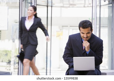 Businessman working outside at laptop outside office