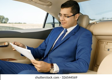 Businessman working with papers in the back-seat of a car