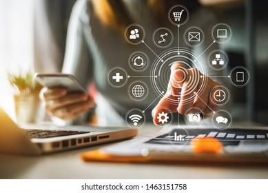 Geschäftsmann, der mit Smartphone, Laptop und digitalem Tablet-Computer arbeitet und digitale Marketingmedien mit virtuellem Symbol nutzt