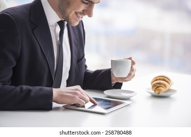 Businessman is working with tablet and drinking coffee and snack.