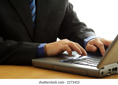 A businessman working and typing on his laptop