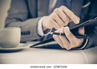 Businessman at the workplace drink coffee and looking some business papers with charts
