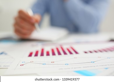 Businessman at workplace office problem with infographics closeup. White collar check money papers stock exchange market earnings list partnership agreement discussion concept
