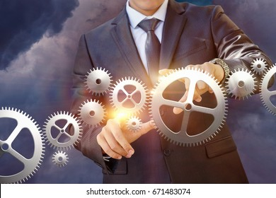Businessman works with a mechanism on sky background.