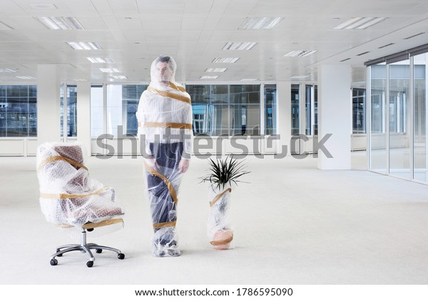 Businessman wrapped in bubble wrap in new office