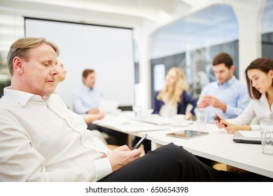 Businessman writes a message with smartphone during a meeting