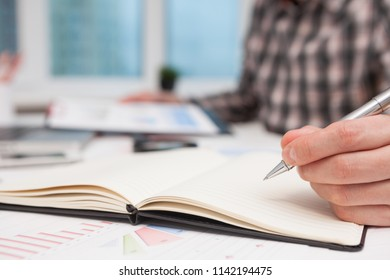 Businessman writes in a notebook while sitting at a desk. Silhouette of cropped shot of businessman hand working with new modern computer and business strategy as concept,selective focus