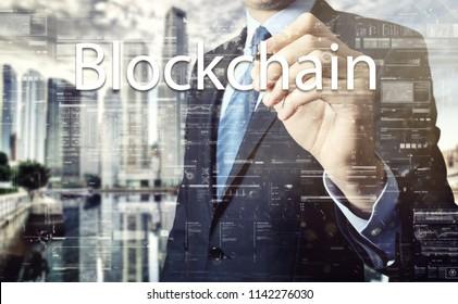 businessman writes a popular buzzword on a virtual whiteboard: Blockchain