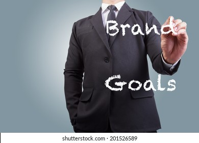 businessman writing brand goals word on the screen by white chalk in business concept