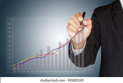 Businessman writing a business graph