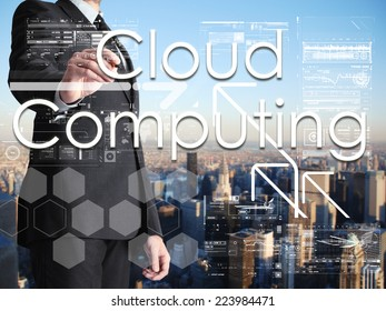 businessman writing Cloud Computing on transparent board with city in background