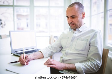 Businessman writing document in creative office